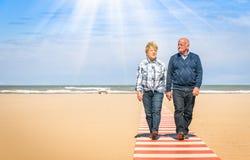 Ευτυχές ανώτερο ερωτευμένο περπάτημα ζευγών χέρι-χέρι στην παραλία Στοκ Φωτογραφία