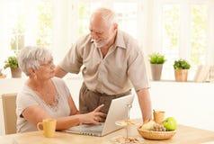 Ευτυχές ανώτερο ζεύγος με τον υπολογιστή στο σπίτι στοκ εικόνες