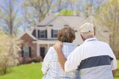Ευτυχές ανώτερο ζεύγος που εξετάζει το μέτωπο του σπιτιού