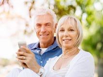 Ευτυχές ανώτερο ζεύγος που εξετάζει το smartphone στοκ φωτογραφία με δικαίωμα ελεύθερης χρήσης