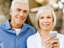 Ευτυχές ανώτερο ζεύγος που εξετάζει το smartphone στοκ φωτογραφία