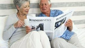 Ευτυχές ανώτερο ζεύγος που διαβάζει μια εφημερίδα απόθεμα βίντεο