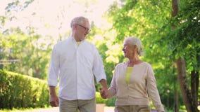Ευτυχές ανώτερο ζεύγος που περπατά στο πάρκο θερινών πόλεων απόθεμα βίντεο