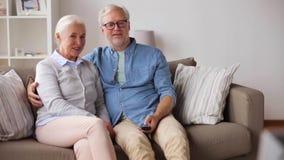 Ευτυχές ανώτερο ζεύγος που προσέχει τη TV στο σπίτι απόθεμα βίντεο