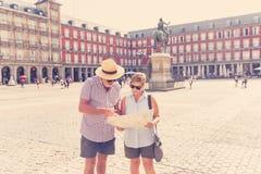 Ευτυχές ανώτερο ζεύγος που ψάχνει τις κατευθύνσεις που χρησιμοποιούν έναν χάρτη στις διακοπές σε μια ευρωπαϊκή πόλη στοκ εικόνα