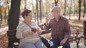 Ευτυχές ανώτερο τσάι συνεδρίασης και κατανάλωσης ζευγών, καφές στο πάρκο πρωινού φθινοπώρου Έχοντας τη συνομιλία και παρουσιάζοντ φιλμ μικρού μήκους