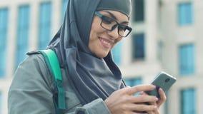 Ευτυχές αραβικό κορίτσι που χρησιμοποιεί το smartphone, που κουβεντιάζει με τους φίλους μετά από τις κατηγορίες στο κολλέγιο φιλμ μικρού μήκους