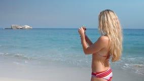 Ευτυχές αρκετά ξανθό κοκτέιλ κατανάλωσης στην παραλία φιλμ μικρού μήκους