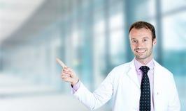 Ευτυχές αρσενικό χαμόγελο γιατρών που δείχνει με το δάχτυλο μακριά επάνω Στοκ Φωτογραφίες
