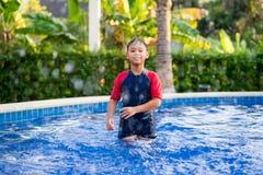 Ευτυχές ασιατικό αγόρι παιδιών που κολυμπά στην πισίνα το καλοκαίρι στοκ εικόνες