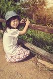 Ευτυχές ασιατικό κορίτσι που χαμογελά και που χαλαρώνει υπαίθρια στην ημέρα, τ Στοκ Εικόνα