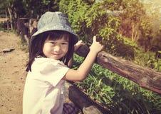 Ευτυχές ασιατικό κορίτσι που χαμογελά και που χαλαρώνει υπαίθρια στην ημέρα, τ Στοκ εικόνα με δικαίωμα ελεύθερης χρήσης