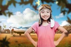 Ευτυχές ασιατικό κορίτσι στο καπέλο αεροπόρων με το τοπίο αεροπλάνων και φθινοπώρου Στοκ εικόνα με δικαίωμα ελεύθερης χρήσης