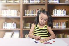 Ευτυχές ασιατικό μικρό κορίτσι που επισύρει την προσοχή σε χαρτί με το κραγιόνι στοκ φωτογραφία