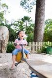 Ευτυχές ασιατικό παίζοντας seesaw αγοριών στην παιδική χαρά στο πάρκο Στοκ Εικόνα
