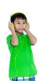 Ευτυχές ασιατικό παιδί με τα ακουστικά, που απομονώνεται στο άσπρο υπόβαθρο Στοκ Εικόνες