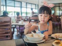 Ευτυχές ασιατικό παιδί που τρώει το εύγευστο νουντλς με chopstick Στοκ Φωτογραφίες