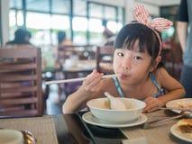 Ευτυχές ασιατικό παιδί που τρώει το εύγευστο νουντλς με chopstick Στοκ Εικόνα