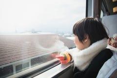 Ευτυχές ασιατικό παιδί που φαίνεται έξω παράθυρο τραίνων έξω Στοκ Φωτογραφία