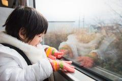 Ευτυχές ασιατικό παιδί που φαίνεται έξω παράθυρο τραίνων έξω Στοκ Φωτογραφίες