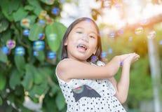 Ευτυχές ασιατικό σαπούνι φυσαλίδων παιχνιδιού κοριτσιών στο σπίτι Στοκ Φωτογραφίες