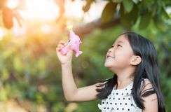 Ευτυχές ασιατικό σαπούνι φυσαλίδων πυροβόλων όπλων παιχνιδιού κοριτσιών στο σπίτι Στοκ Εικόνες