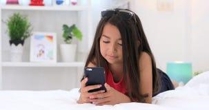 Ευτυχές ασιατικό χαριτωμένο παιχνίδι κοριτσιών στο έξυπνο τηλέφωνο με το πρόσωπο χαμόγελου στο σπίτι φιλμ μικρού μήκους