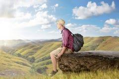 Ευτυχές ασιατικό backpacker με τη συνεδρίαση καπέλων στον απότομο βράχο ακρών Στοκ εικόνα με δικαίωμα ελεύθερης χρήσης