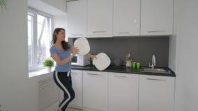 Ευτυχές αστείο γυναικών νοικοκυρών γύρω και τραγουδά με τα πιάτα στα όπλα στην κουζίνα στο σπίτι απόθεμα βίντεο