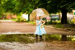 Ευτυχές αστείο κορίτσι παιδιών με την ομπρέλα που πηδά στις λακκούβες στις λαστιχένιες μπότες και στο φόρεμα και το γέλιο στοκ φωτογραφίες με δικαίωμα ελεύθερης χρήσης