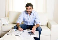 Ευτυχές λατινικό άτομο που πληρώνει τους λογαριασμούς και την πιστωτική κάρτα στον καναπέ στοκ φωτογραφία με δικαίωμα ελεύθερης χρήσης