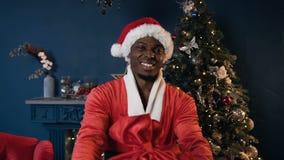 Ευτυχές αφρικανικό άτομο στο κοστούμι Άγιου Βασίλη που κρατά το δώρο στο υπόβαθρο χριστουγεννιάτικων δέντρων απόθεμα βίντεο