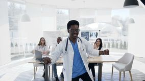 Ευτυχές αφρικανικό αρσενικό που χορεύει κατά τη διάρκεια της ημέρας εργασίας με την ομάδα του cowoker στο υπόβαθρο στο νοσοκομείο φιλμ μικρού μήκους