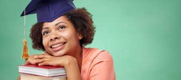 Ευτυχές αφρικανικό κορίτσι αγάμων με τα βιβλία στο σχολείο Στοκ Εικόνα