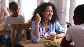 Ευτυχές αφρικανικό κορίτσι που απολαμβάνει την ημερομηνία με το μαύρο τύπο στον καφέ απόθεμα βίντεο