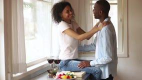 Ευτυχές αφρικανικό ρομαντικό νέο ζεύγος που έχει τη διασκέδαση που αγκαλιάζει στην κουζίνα φιλμ μικρού μήκους