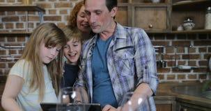 Ευτυχές βίντεο οικογενειακών ρολογιών στην ψηφιακή ταμπλέτα στην κουζίνα κατά τη διάρκεια των μαγειρεύοντας γονέων με δύο παιδιά  απόθεμα βίντεο