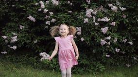Ευτυχές γέλιο αστείο λίγο κοριτσάκι που πηδά στο θερινό κήπο σε αργή κίνηση φιλμ μικρού μήκους