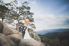 Ευτυχές γαμήλιο ζεύγος που φιλά και που αγκαλιάζει κοντά σε έναν υψηλό απότομο βράχο στοκ φωτογραφία