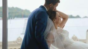Ευτυχές γαμήλιο ζεύγος που χαλαρώνει και που αγκαλιάζει στον εκλεκτής ποιότητας καφέ Έννοια ημέρας γάμου κλείστε επάνω Πανοραμική απόθεμα βίντεο