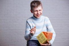 Ευτυχές γελώντας αγόρι με το σπίτι παιχνιδιών χαρτονιού στα χέρια Παιδική ηλικία στοκ φωτογραφία με δικαίωμα ελεύθερης χρήσης