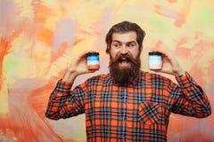 Ευτυχές γενειοφόρο άτομο που κρατά δύο καλλυντικά βάζα Στοκ Εικόνες