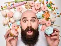 Ευτυχές γενειοφόρο κέικ κρέμας δαγκώματος ατόμων στο άσπρο υπόβαθρο στοκ εικόνα με δικαίωμα ελεύθερης χρήσης