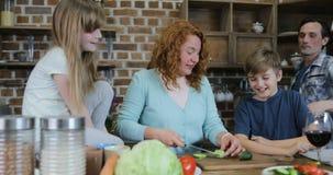 Ευτυχές γεύμα Cook μητέρων οικογενειακής βοήθειας μαζί στους γονείς κουζινών με δύο παιδιά που μιλούν προετοιμάζοντας τα τρόφιμα  φιλμ μικρού μήκους