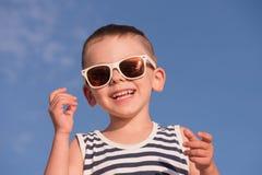 Ευτυχές γελώντας μικρό παιδί που φορά το πουκάμισο γυαλιών ηλίου και λωρίδων ναυτικών Στοκ εικόνες με δικαίωμα ελεύθερης χρήσης