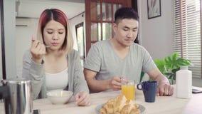 Ευτυχές γλυκό ασιατικό ζεύγος που έχει το πρόγευμα, τα δημητριακά στο γάλα, το ψωμί και το χυμό από πορτοκάλι κατανάλωσης μετά απ
