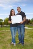 Ευτυχές διαφυλετικό ζεύγος με το κενό σημάδι στοκ φωτογραφία με δικαίωμα ελεύθερης χρήσης