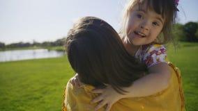 Ευτυχές ειδικό κορίτσι αναγκών που τρέχει και που αγκαλιάζει mom απόθεμα βίντεο