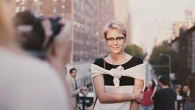 Ευτυχές ειρηνικό ευρωπαϊκό ξανθό κορίτσι με την κοντή τρίχα eyeglasses που χαμογελά στο photoshoot έξω, που θέτει στη κάμερα απόθεμα βίντεο