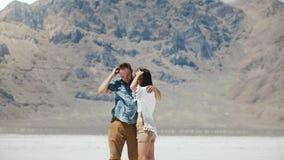 Ευτυχές ελκυστικό ρομαντικό αγκάλιασμα στάσεων ζευγών μαζί, που φιλά στην επική άσπρη επίπεδη αλατισμένη έρημο Bonneville Γιούτα απόθεμα βίντεο